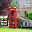 Telephone booth and bench in English countryside of Cotswolds — Stock Photo #65484595