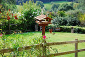 Birdhouse with flowers of pastoral garden in Cotswolds, England — Stock Photo