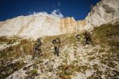 Soldiers team up the hill with a guide — Stock Photo