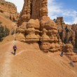 Постер, плакат: A Young Man and Two Young Women explore the Colorful Rock Formations of Red Canyon Utah