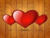 Three red glossy heart on a wooden background — Stock Vector