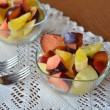Mixed fruit salad in the bowl on the wooden table — Stock Photo #62453587