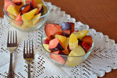 Mixed fruit salad in the bowl on the wooden table — Stock Photo