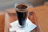 Black coffee in glass on the wooden table — Stock Photo
