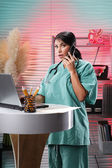 Doctor working on laptop and talking on phone — Stock Photo