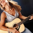 Girl playing on an acoustic guitar — Stock Photo #64591197