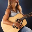 Girl playing on an acoustic guitar — Stock Photo #64594807
