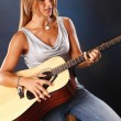 Girl playing on an acoustic guitar — Stock Photo #64594961