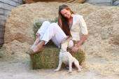Girl plays with her pet at the barn — Stock Photo