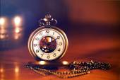 Retro gold pocket watch in beautiful  light candle  on brown background — Stock Photo