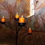 Candles burning on black candleholder inside ancient fresco walls — Stock Photo #68714221