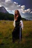 A young beautiful woman with blonde hair in historical dress is posing in an enchanting open landscape with trees and a mountain meadow, with a hand-to-heart gesture and mystical medieval sword. — Stock Photo