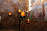 Candles burning on black candleholder inside ancient fresco walls — Stock Photo