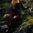 Beautiful woman fairy with long blonde hair in a historical gown is sitting amids moos covered rocks in enchanting forestral landscape — Stock Photo #68746243