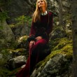 Beautiful woman fairy with long blonde hair in a historical gown is sitting amids moos covered rocks in enchanting forestral landscape — Stock Photo #68746311