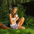 Young beautiful woman with blonde hair is holding lovingly a stray dog in her arms  sitting in a backyard garden with green grass — Stock Photo #68746335