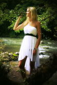 Beautiful young woman in a radiant white summer dress posing in a forest landscape with a river — Foto Stock