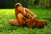 Young beautiful woman with blonde hair is holding lovingly a stray dog in her arms  sitting in a backyard garden with green grass — Stock Photo
