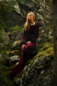 Beautiful woman fairy with long blonde hair in a historical gown is sitting amids moos covered rocks in enchanting forestral landscape — Stock Photo