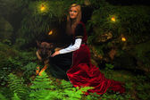 A beautiful woman fairy with long blonde hair in a historical gown, with dog — Stock Photo