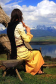 A beautiful girl in a historical costume playing her flute in an open landscape with a lake — Stock Photo