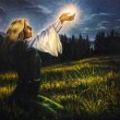 Beautiful painting oil on canvas of a mystical young woman in green emerald medieval dress is holding a glowing ball of light in her palms amids a nocturnal meadow — Stock Photo #68772189
