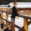 A beautiful young blonde lady posing on a wooden balustrade in a snowy winter landscape — Stock Photo #69863679