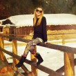 Beautiful young blonde lady posing on a wooden balustrade in a snowy winter landscape. — Stock Photo #69863715
