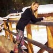 Beautiful young blonde lady posing on a wooden balustrade in a snowy winter landscape. — Stock Photo #69863737