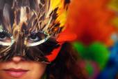 Young woman with a colorful feather carnival face mask on bright colorful background, eye contact, make up artist — Stock Photo