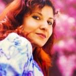 Beautiful lady on sakura blossom background, pink flowers, Orange Feathered earring — Stock Photo #72041091