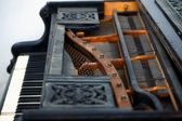Old piano detail with keyboard, wooden carved ornament and mechanics — Stock Photo