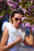 Beautiful Girl with flowers, Spring Magic. Sakura pink flowers. With glamour white fur, and sunglasses — Stock Photo