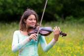 Violinist on a meadow full of flowers, Young girl playing music instrument — Stock Photo