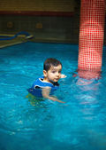 Young boy with inflatable swimming vest in the pool, has a happy smile.  Eye contact. — Stock Photo