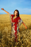 Smiling Young woman with ornamental dress standing on a wheat field with sunset. Natural background and blue sky. — Stock Photo
