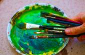 Paint brushes in man hand to the painting palette with colors — Stock Photo