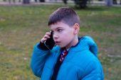 Boy in blue jacket talking on the phone — Stock fotografie