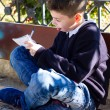 Boy carefully writes in a notebook — Stock Photo #65734137