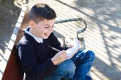 Boy in the park makes lessons — Stockfoto