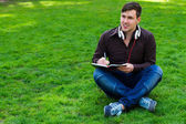 The guy on the grass writes in a notebook — Foto Stock