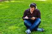 The guy on the grass writes in a notebook — Foto de Stock