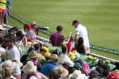Cricketer with autograph seekers — Stock Photo