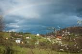 Rainbow over small village — Foto de Stock