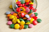Colorful sugar-coated chocolate smarties in a glass — Stock Photo