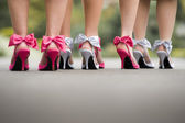 Close up of group of ladies wearing colourful bow heel shoes on tarmac — Stock Photo