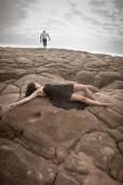 Beautiful couple flirting and having fun together on beach rocks — Photo
