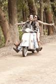 Young attractive couple traveling by scooter along dirt road — Стоковое фото