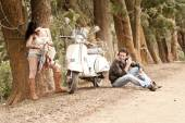 Young attractive couple flirting and traveling by scooter along dirt road — Stock Photo