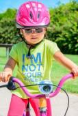 Girl wearing   riding bike — Stock fotografie